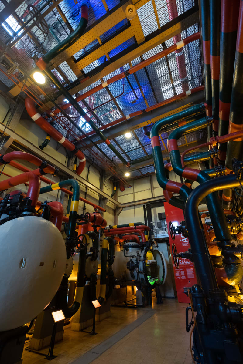 An interior photo of some boilers in Maat. The room is filled with pipes of all sizes and is generally painted in bright primary colours.