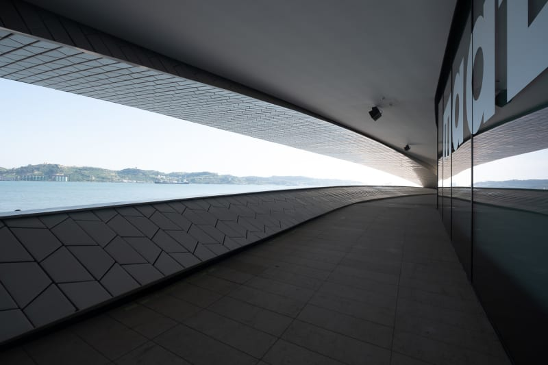 A photo taken from the exterior walkway of the new Maat gallery. On the right is the glass exterior wall of the gallery with the letters 'maat' visible in large white text. On the left the Tagus river and shore of Porto Brandão can be seen through a long cut away in the walkway.