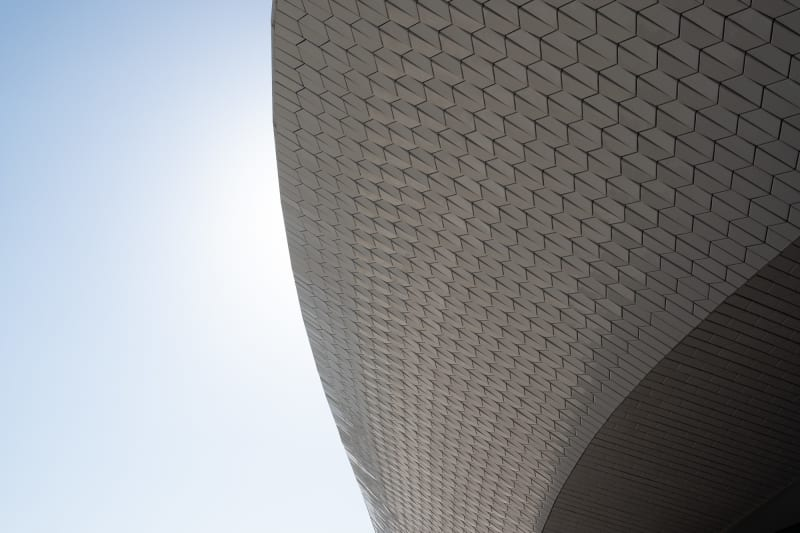 A close cropped detail of the Maat ceiling. the ceiling is in a flowing curved form and covered in small tiles. A cloudless sky can be seen behind.