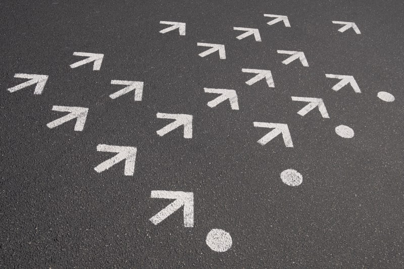 18 small white arrows are painted on a stretch of tarmac. They all point the same way.