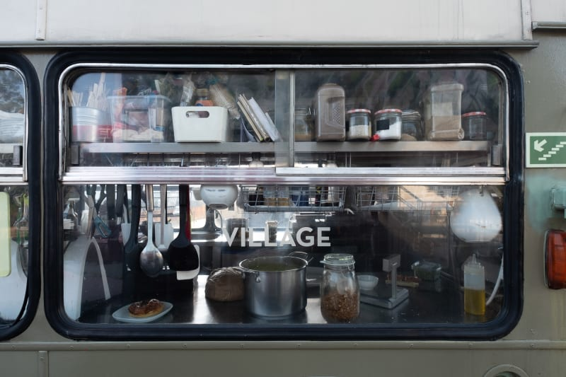 Looking straight on to a bus window. The interior of the window reveals the contents of a small working kitchen. The text 'village' is visible in white text in the middle of the window.