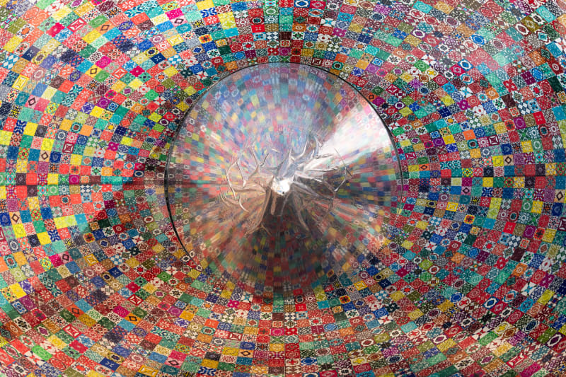 A round silver cone points directly at the camera. Iit is surrounded by a colourful mosaic print. It reflects some of the colours from the print.