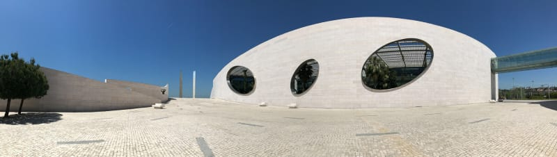 A panorama in bright sunlight of the Champalimaud Foundation courtyard. On the right the large main wall of the building is visible with three large oval openings cut away.