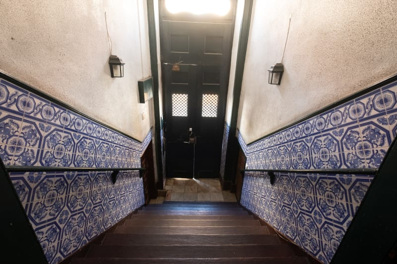 A wide angle photo looking down an interior staircase to the front door of a building. The staircase is steep, and on either side the walls are covered to shoulder height with blue and white patterned tiles.