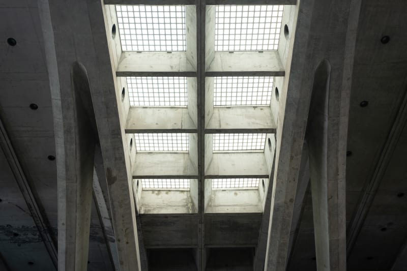 Looking up at skylight windows in a train station. The ceiling is cast concrete, and the lights are made from a grid of glass tiles.