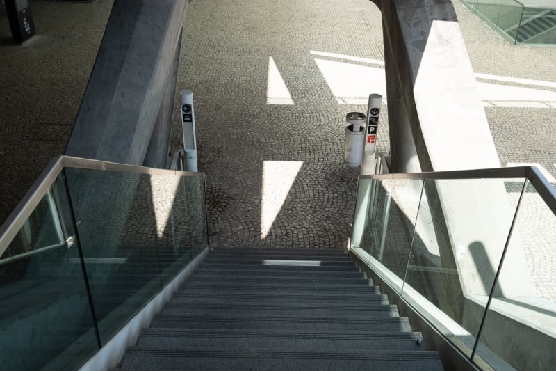 Looking down a staircase in a train station. The base of the stairs has an irregular tiled pattern.