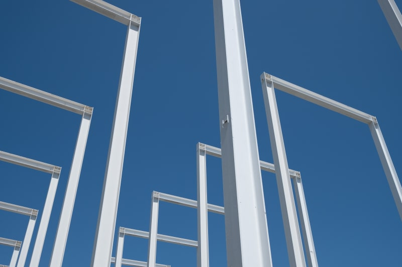 White steel beams in the shape of rectangles 50′ tall are spaced regularly 20′ appart. The camera looks up from the corner at the regular white grid this makes against the blue sky.