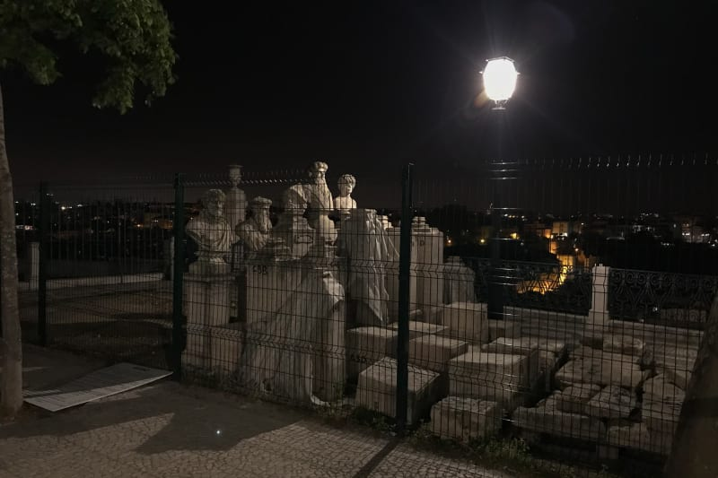 A group of tall marble statues are arranged in a tight grid and surrounded by tall fencing. They're lit from one side by a streetlamp.