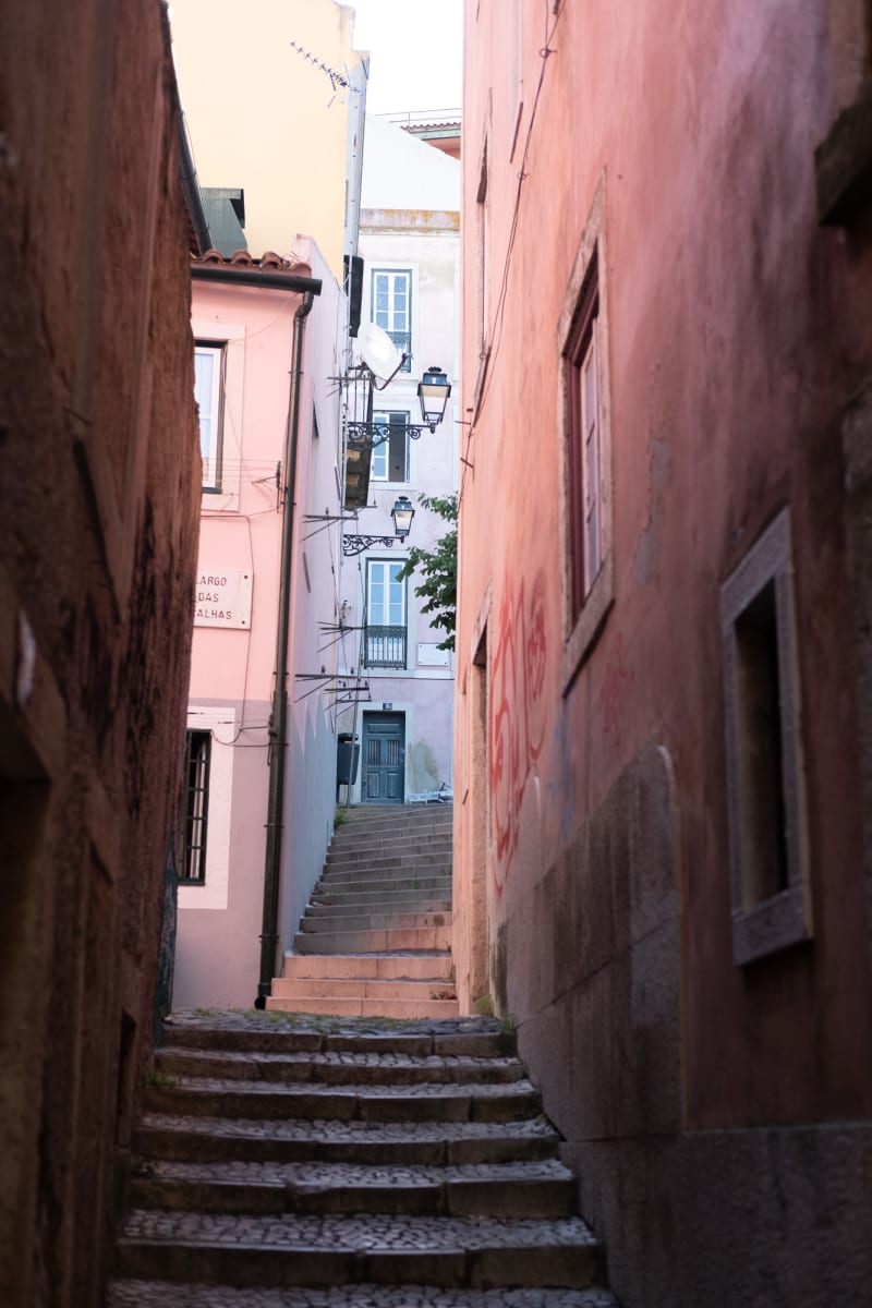 Looking up a narrow alleyway filled with two flights of steps. The buildings on each side are painted in light pink pastel colours