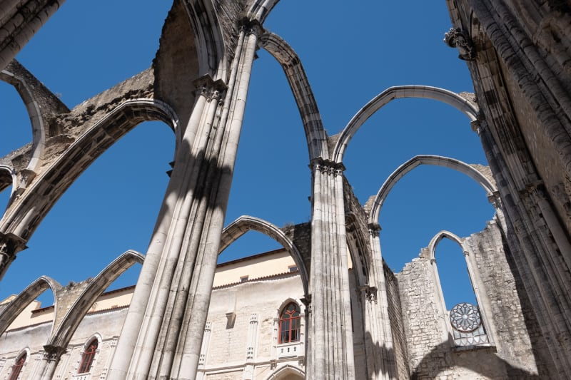 Looking up at the ruins of the Carmo Convent. All that remains are the arches of the building, with blue sky where the ceiling would be.