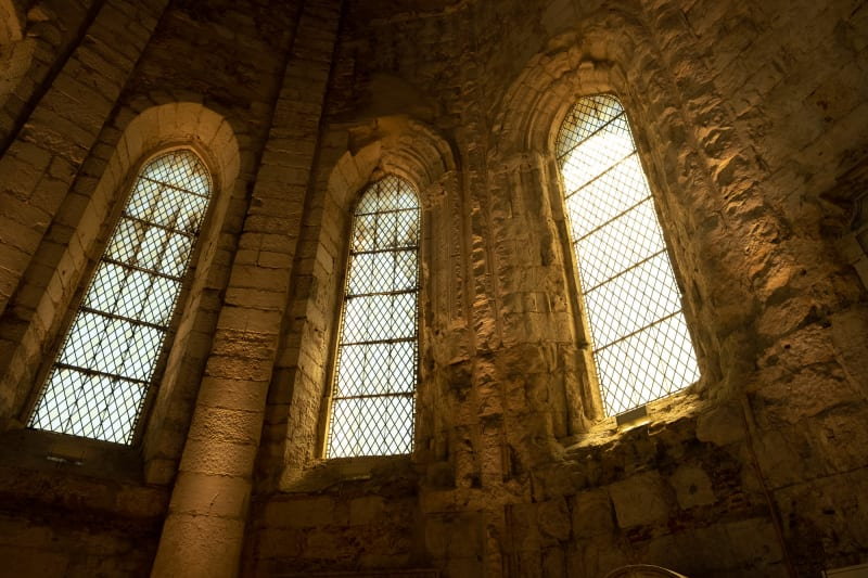 An interior view of three windows in the Carmo Convent - the interior is dark but warmly lit by the three windows.