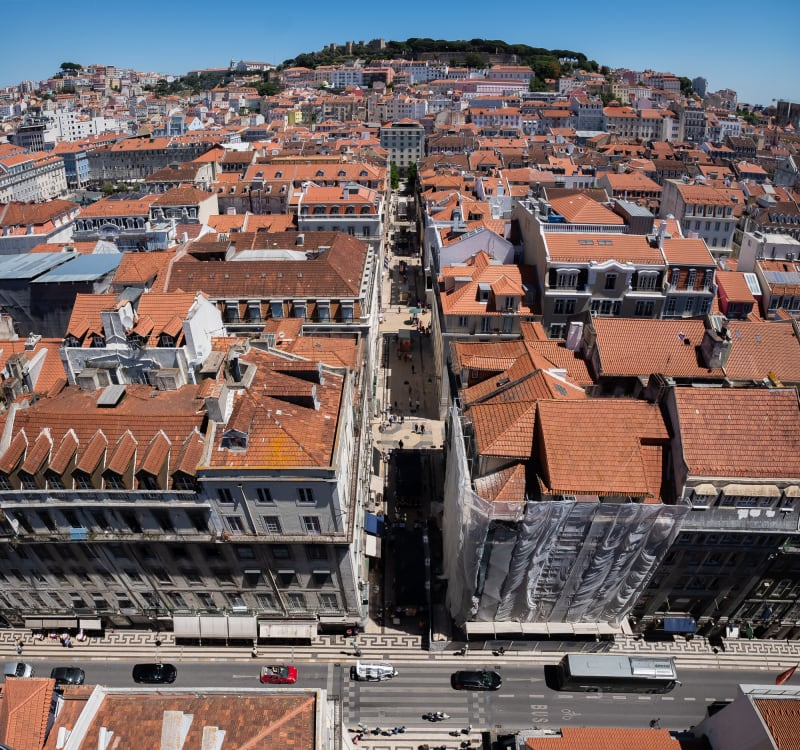 A square panorama looking down from high up to the streets of Lisbon. Down the centre of the frame a pedestrian street recedes. At the bottom of the frame is a large road.