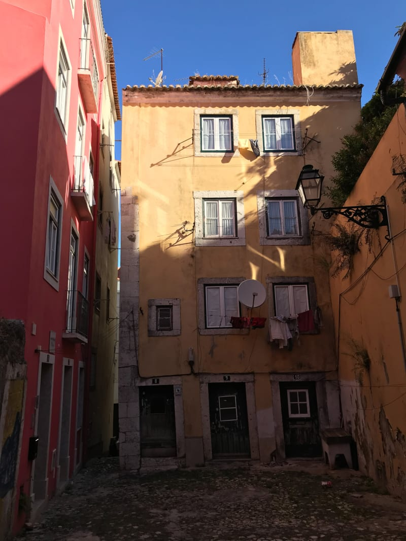 A portrait photo of the entrance to a 4 storey building at the end of a wide alleyway. The building is painted in pastel-yellow, and has a pastel pink building to the left.
