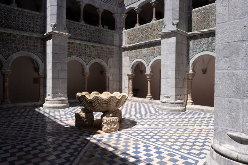 A view of the open-air courtyard in the centre of Pena Palace. The courtyard has blue and white checkerboard tiles, and a large fountain in the shape of a shell in the center.