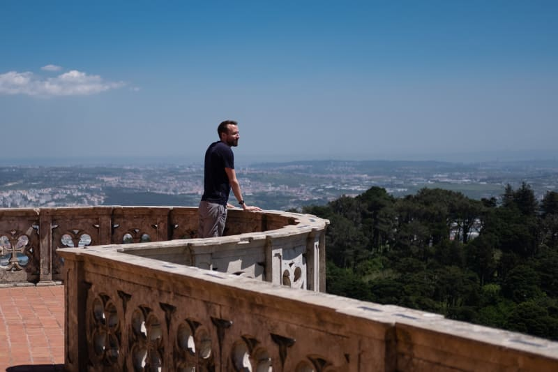 A photo of Ed Horsford looking out over a round balcony to the landscape of Sintra beyond