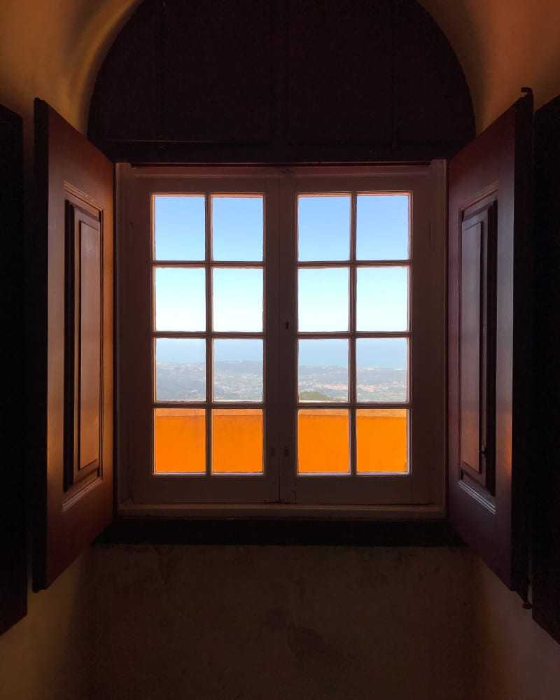 Looking from inside to a window looking out on a high vista. The interior is dark with dark wood window frame. Through the window the sky outside is bright. The window is made from two sets of 2x4 small glass frames. The bottom row is bright orange from an balcony outside.