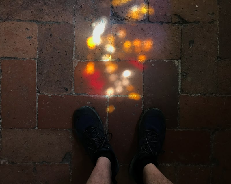 Looking down at a parque brick floor. At the base of the image are the photographer's feet. Above them is speckled bright dots of light.