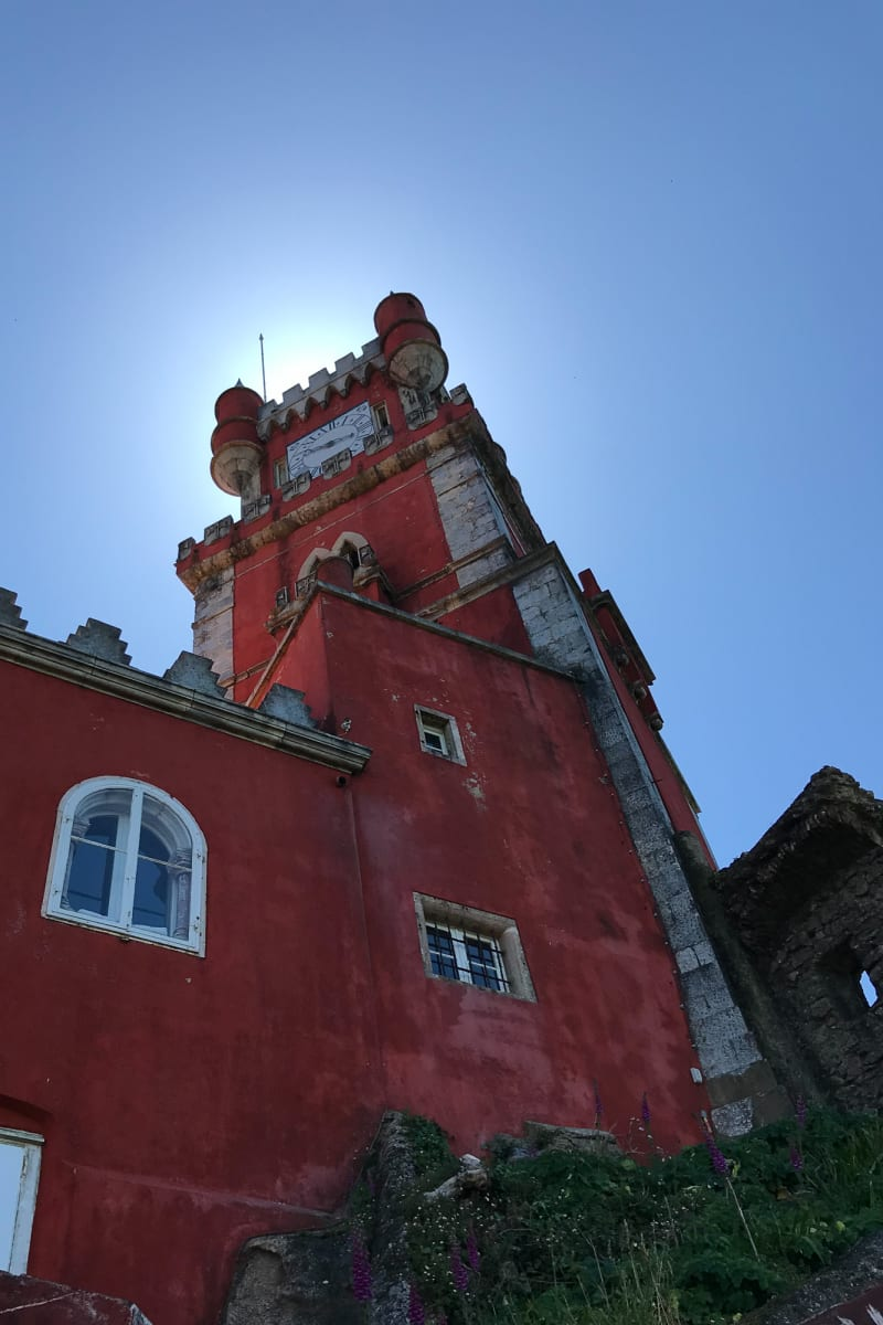 Looking up at a tall ornate red building in Pena palace.