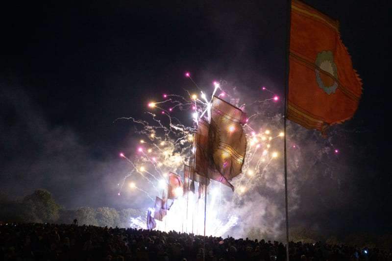 Fireworks in front of the Glastonbury flags.