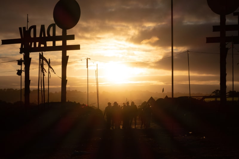 Sunrise over glastonbury festival. The sun is directly ahead silhouetting people walking home.