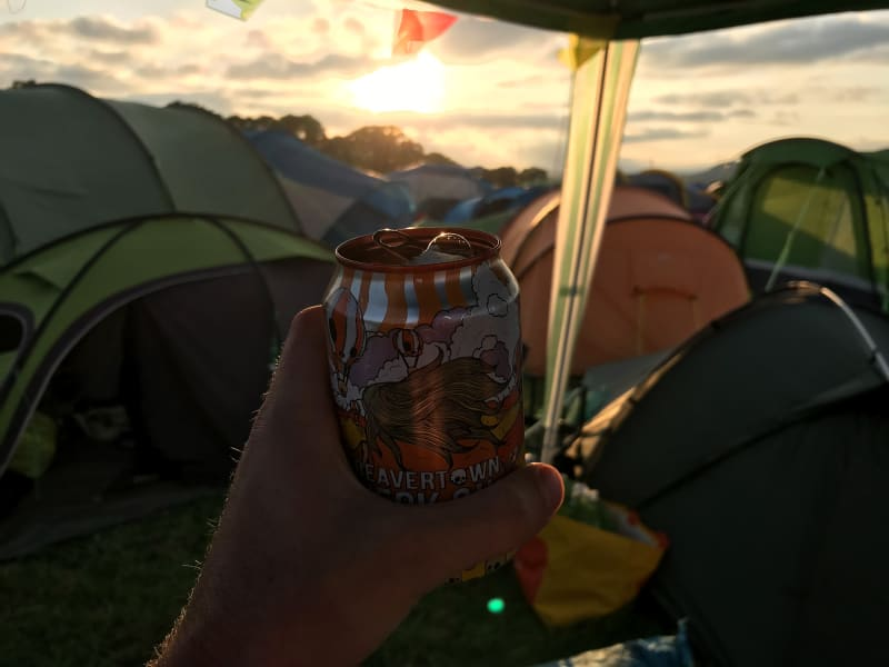 Holding a Beavertown beer can in golden sunset by a group of tents.