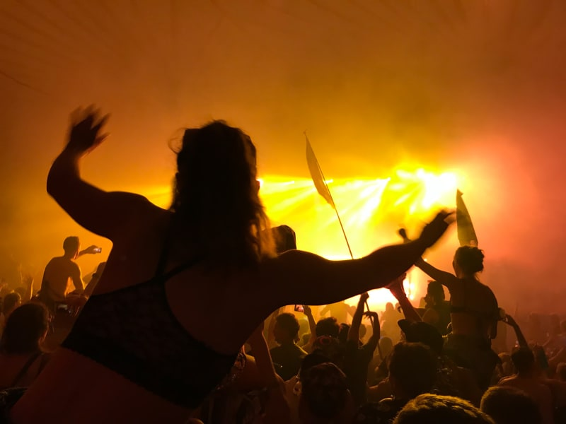 A music fan sits on a friend's shoulders and sways in the yellow smoky light in front of the stage.