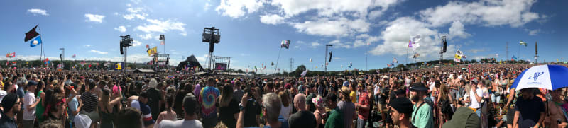 A panorama of a crowd of people in front of the Pyramid stage.