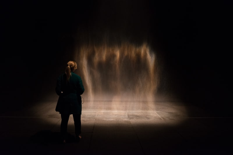 A fine mist of water drops in a dark room, lit from the side. A woman stands in front of the artwork.