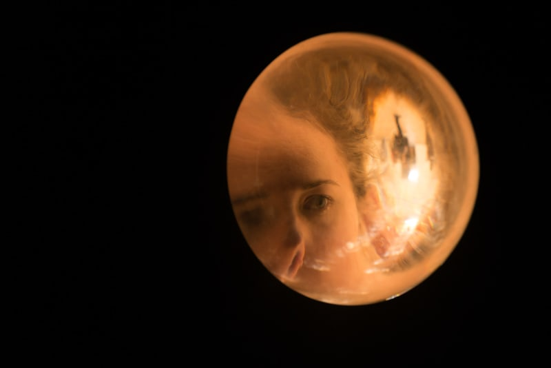 A solid sphere of glass fills the right frame of the photo, set against black. There's an image of a woman's face magnified inside the glass.