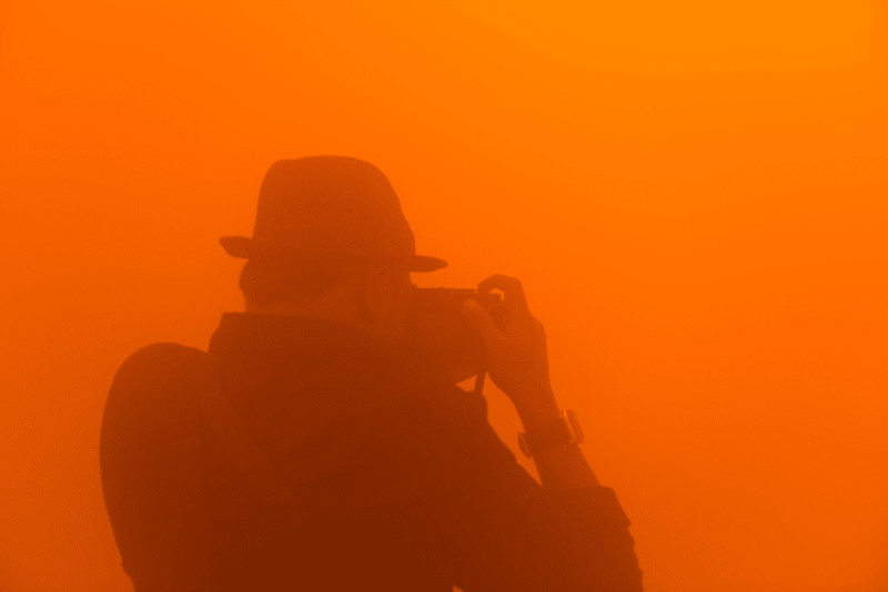 A photographer wearing a hat composes a photo inside an orange foggy room.