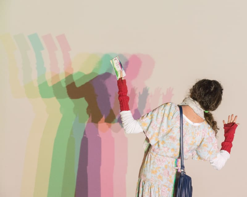 A woman stands in front of a white wall. A light shines on her from behind, casting a multi-coloured shadow on the wall.