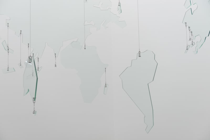 A large mobile made from sheets of glass cut in to shapes of continents, forming a glass map of the world.