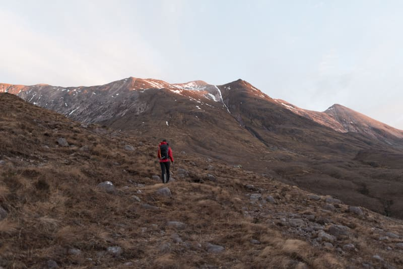 Chris walking away from the camera and towards Beinn Eighe, just at sunrise.