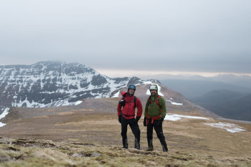 Chris and Ed pose for a photo on top of Beinn Eighe. They both have heavy jackets and helmets on.