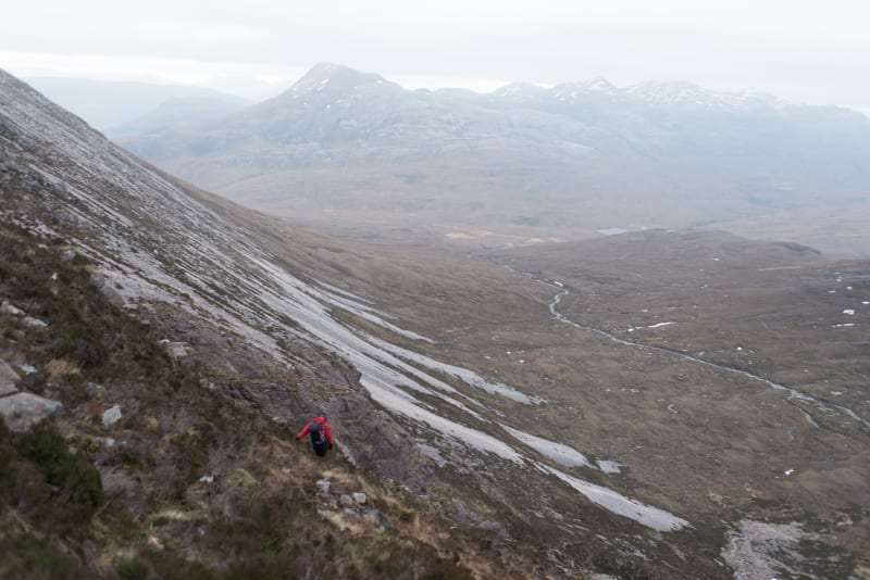 A photo taken from mid-way up Beinn Eighe, pointing down. Chris is ahead, descending the mountain.