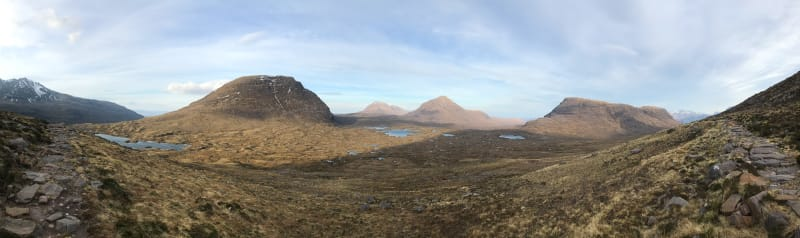 Panorama from side of Beinn Eighe. The landscape is brown with patches of green in a partially sunny day.