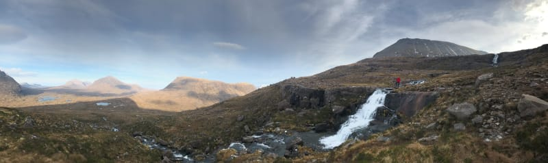 A panorama from the base of Beinn Eighe, looking north. In the right of the frame a small waterfall flows left. Chris is stood at the top of the waterfall in a bright red jacket.