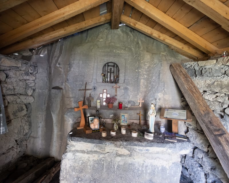 Looking inside a small chapel. The inside is bare except for a few religious artefacts on a cement table.