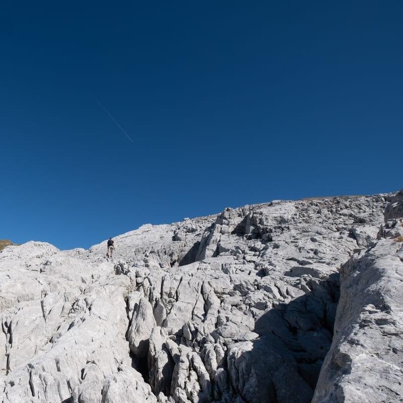 Oj climbs deeply creased rocks under a deep blue sky.