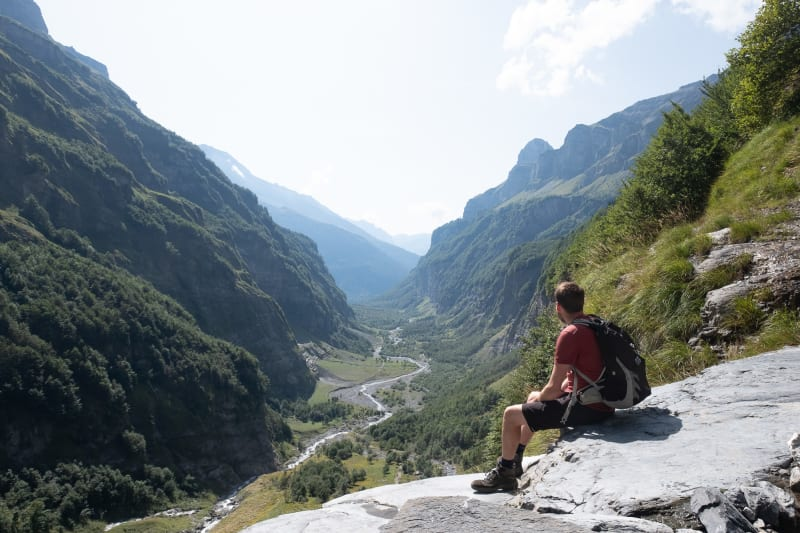 Ed sat on a large rock, overlooking a large and deep valley.