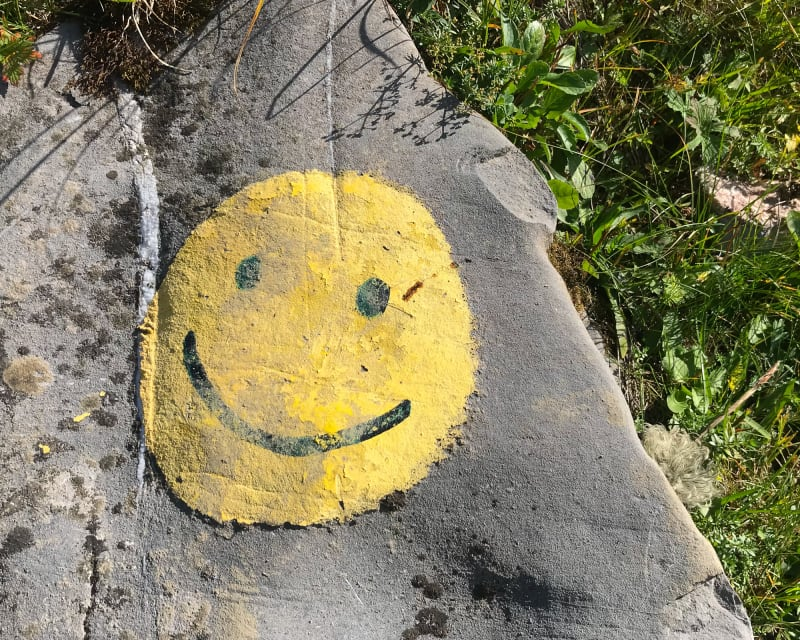 A yellow circle painted on a rock, with a smiling face in the middle.