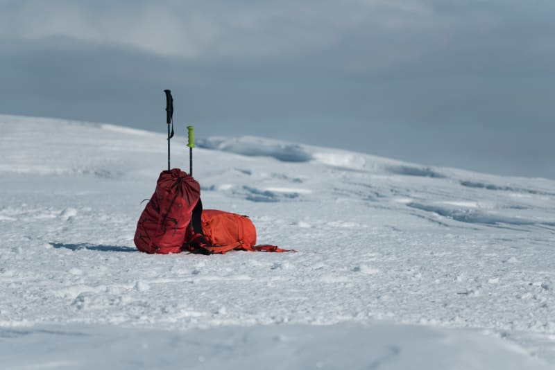 Two climbing bags lean against each other - deserted on a snowy plateau.