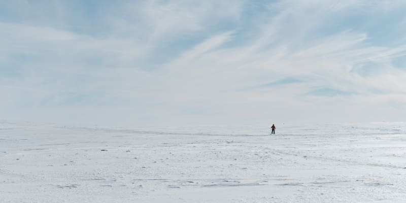 A lone cross country skier on an otherwise flat and snowy plateau.