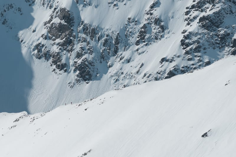 A high zoom photo looking towards a section of the CMD arete on a sunny day. Tiny figures can be seen descending it.