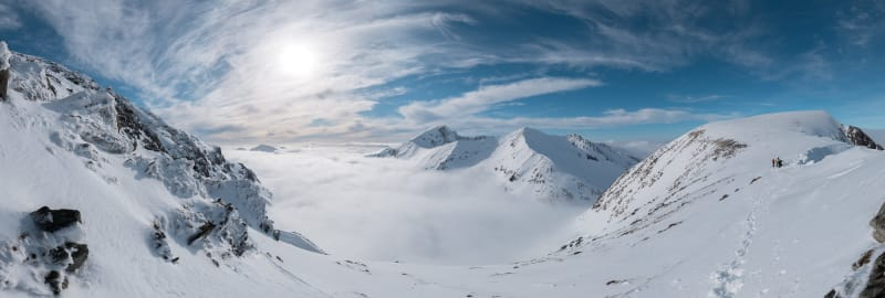 A panorama taken from Aonach Mòr looking towards Ben Nevis. The sky is sunny and deep blue, and there's a cloud inversion, so the ground isn't visible.