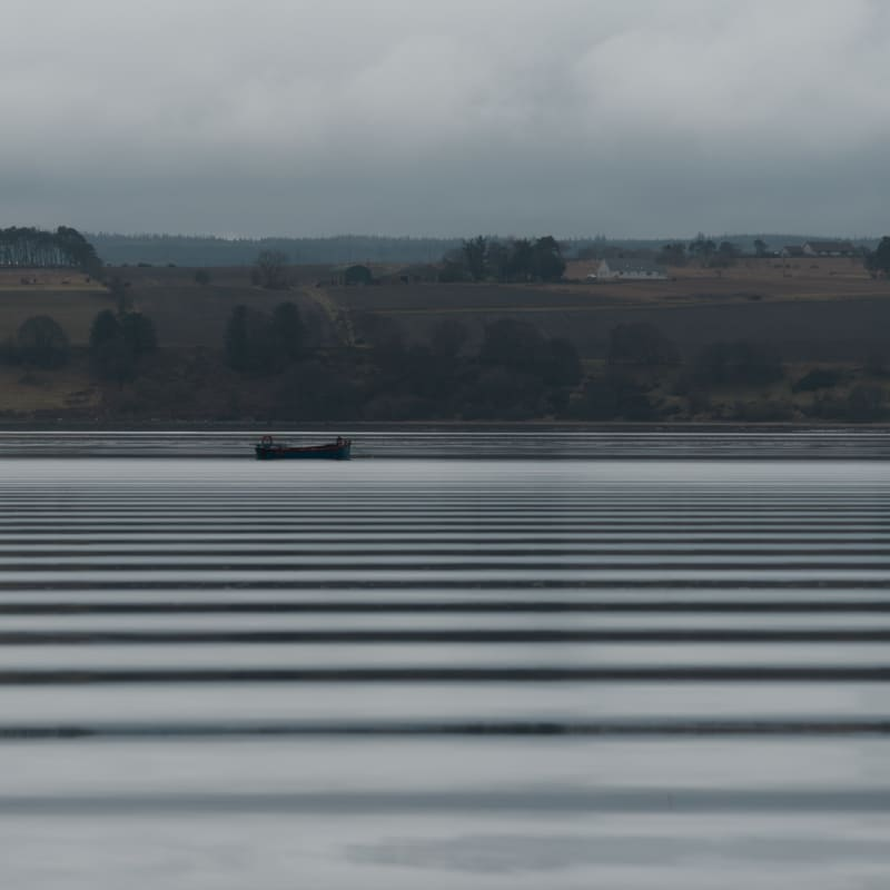 Looking across a wide lake on a grey day. In the distance is a small industrial boat. The water has regular horizontal dark bands - like a barcode - caused by ripples from a passing boat.