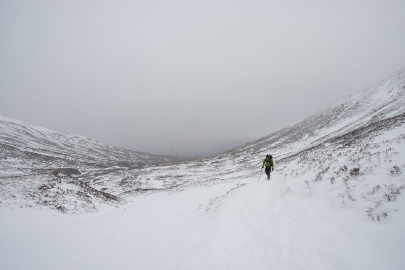 looking down a snowy hill with low grey clouds. Ed is off to one side walking up towards the camera.