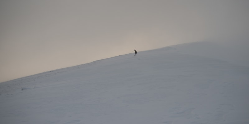A wide shot at dusk looking up a snowy hill. A figure (Ed) in the distance can be seen waving an ice axe.