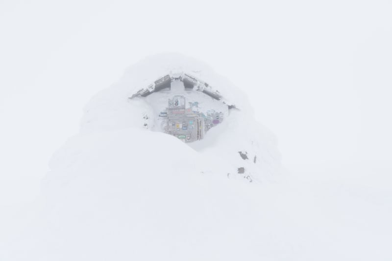 The emergency hut at the top of Ben Nevis. It's covered in lots of snow, so only a patch of the top of the doorway is visible. There's low visibility so it looks somewhat ghostly.