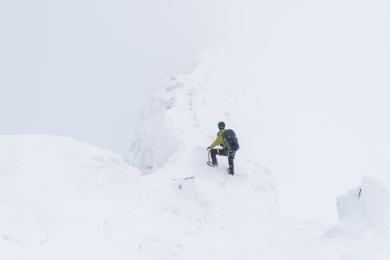 Chris at the start of the CMD Arete, going down. It's very snowy with low visibility. The ridge is only just visible.